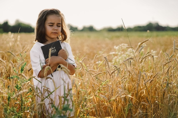 Het meisje houdt bijbel in haar handen. de bijbel lezen in een veld. concept voor geloof, spiritualiteit en religie. vrede, hoop