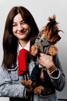Het meisje houdt bruine geïsoleerde hond. jonge aantrekkelijke vrouw met hond yorkshire terrier glimlacht. foto dichten. verzorging van huisdieren. mensen en huisdieren.