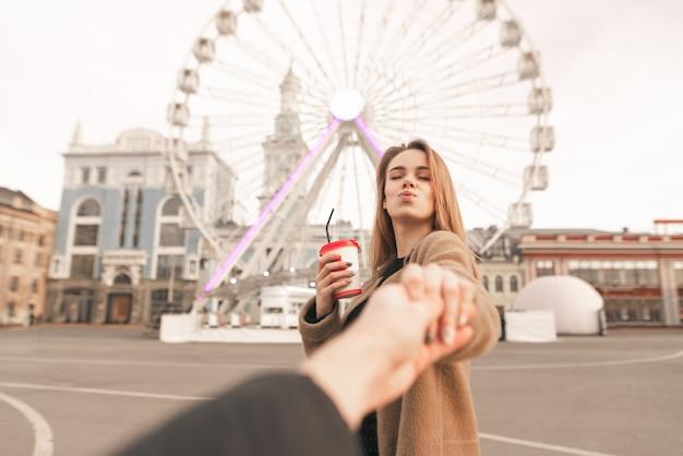 Het meisje houdt de hand van haar vriend vast en maakt een luchtkus tegen de achtergrond van het stadslandschap. liefde. volg mij