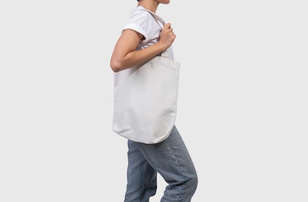 Het meisje houdt de stof van het zakcanvas voor geïsoleerd mockup leeg malplaatje