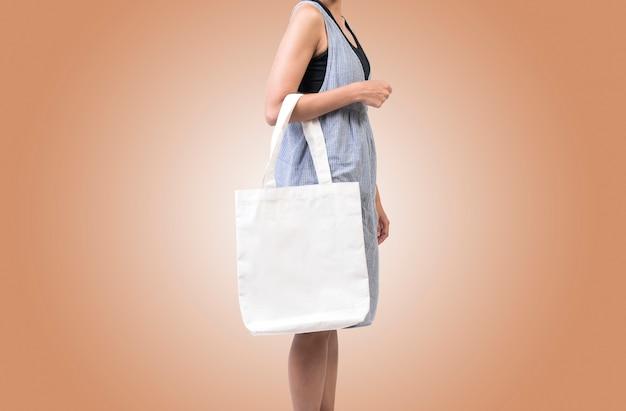 Het meisje houdt de stof van het zakcanvas voor model leeg die malplaatje op kleurenachtergrond wordt geïsoleerd.