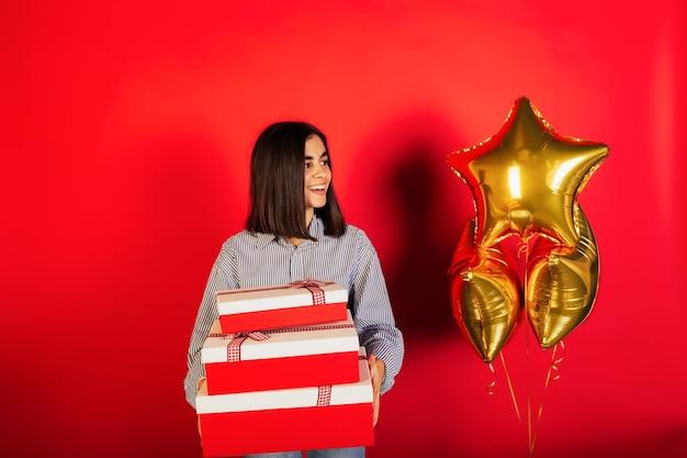 Het meisje houdt drie rode geschenkdozen en helium gouden ballonnen op rode achtergrond.