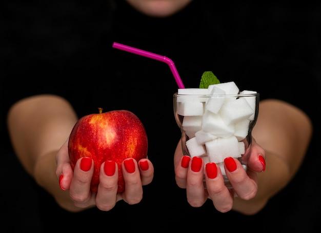 Het meisje houdt een appel en een glas met suiker, menselijke keus, gezond en ongezonde kost