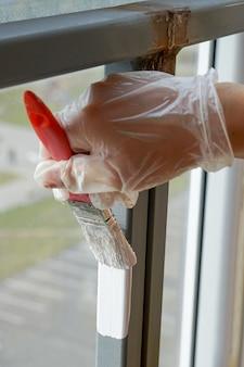 Het meisje houdt een borstel met een rode pen in haar hand en gaat het balkonleuning met witte verf schilderen