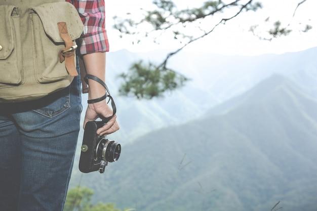 Het meisje houdt een camera vast, wandelt in het tropische bos, samen met rugzakken in het bos, avontuur, reizen, toerisme, klimwandeling.