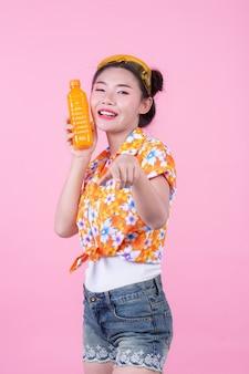 Het meisje houdt een fles sinaasappelsap op een roze achtergrond.