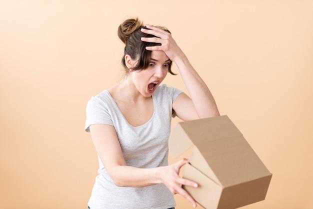 Het meisje houdt een kartonnen doos op armlengte vast en houdt haar hoofd vast.