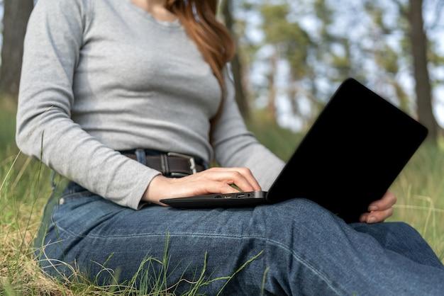 Het meisje houdt een laptop op schoot. buiten werk. Premium Foto