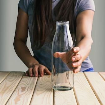 Het meisje houdt een lege fles voor een dieetdrank