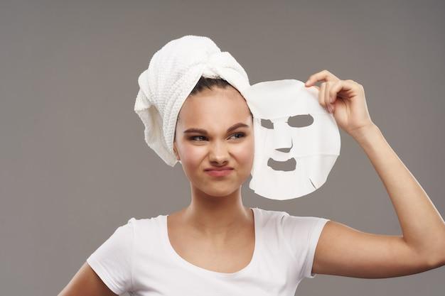 Het meisje houdt een masker in haar hand om de huid te reinigen