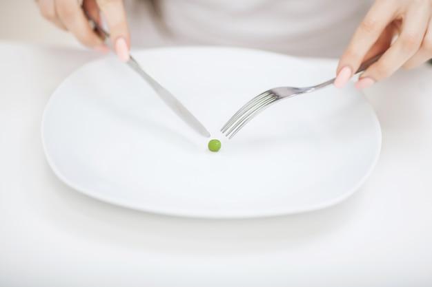 Het meisje houdt een plaat en probeert een erwt op de vork te zetten