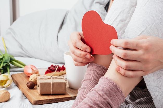 Het meisje houdt een rood hart vast. gefeliciteerd met valentijnsdag op 14 februari. ontbijt op bed en een cadeau.