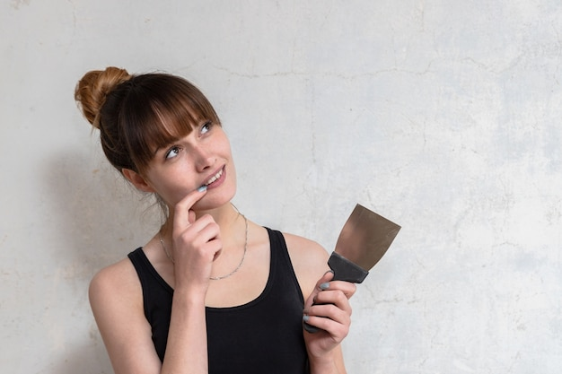 Het meisje houdt een spatel in zijn hand. het concept van nadenken over renovatie-ideeën. nadenkend gezichtsuitdrukking.