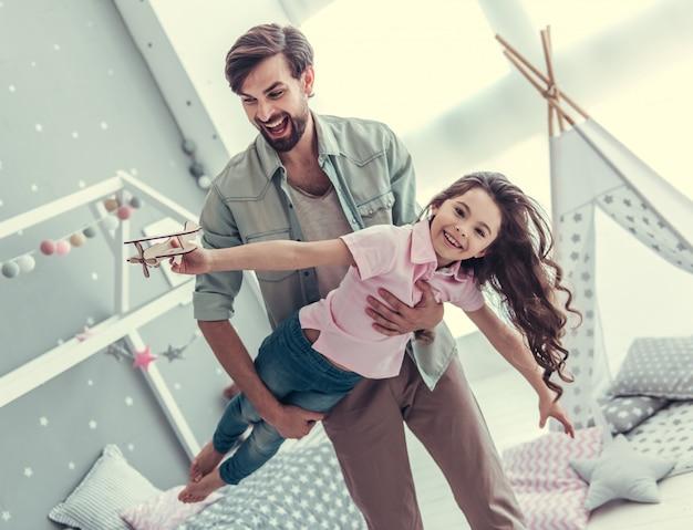 Het meisje houdt een speelgoedvliegtuig en papa houdt zijn dochter vast.