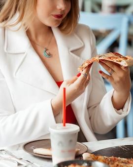 Het meisje houdt een stuk knapperige pizza in haar hand