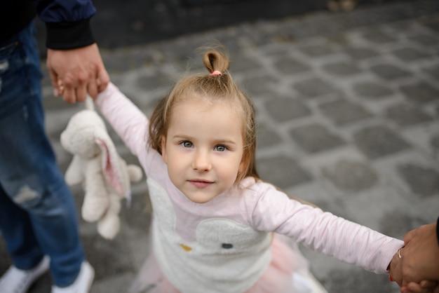 Het meisje houdt een stuk speelgoed en handen van de ouders. close-up. meisje glimlacht in het frame.