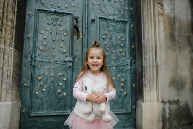 Het meisje houdt een stuk speelgoed konijntje in haar handen en glimlacht. detailopname. meisje poseren op de achtergrond van de deuren van de oude kerk.