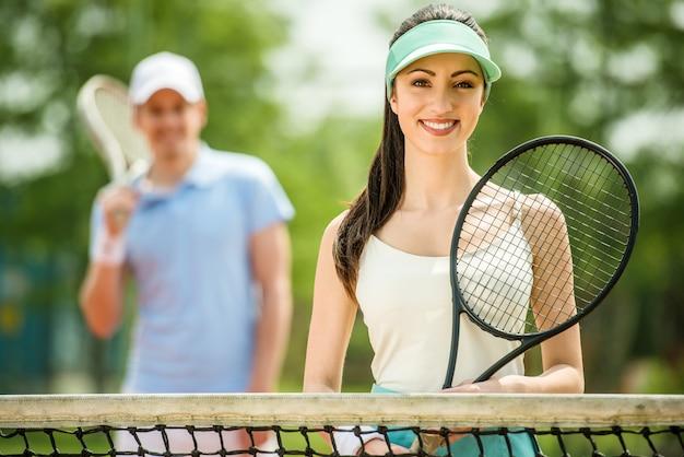 Het meisje houdt een tennisracket en glimlacht.