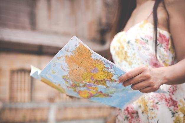 Het meisje houdt een toeristenkaart in de oude stad.