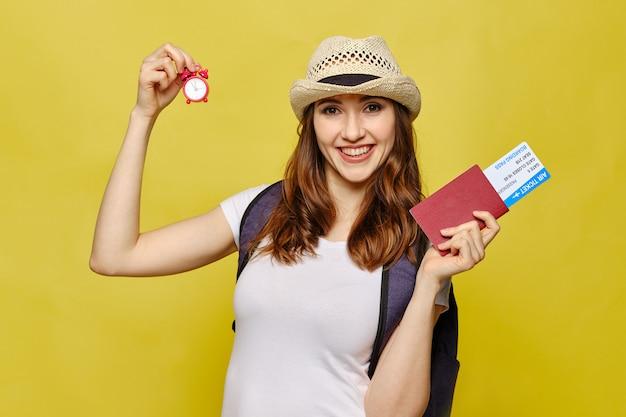 Het meisje houdt een uur en vliegtickets met een paspoort op een gele achtergrond.