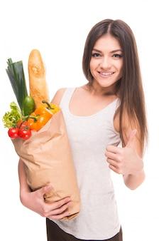 Het meisje houdt een zak groenten en glimlacht.