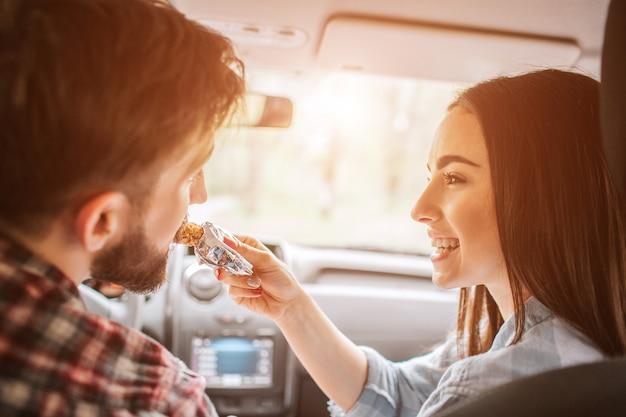 Het meisje houdt een zoete reep en voedt het aan haar vriend