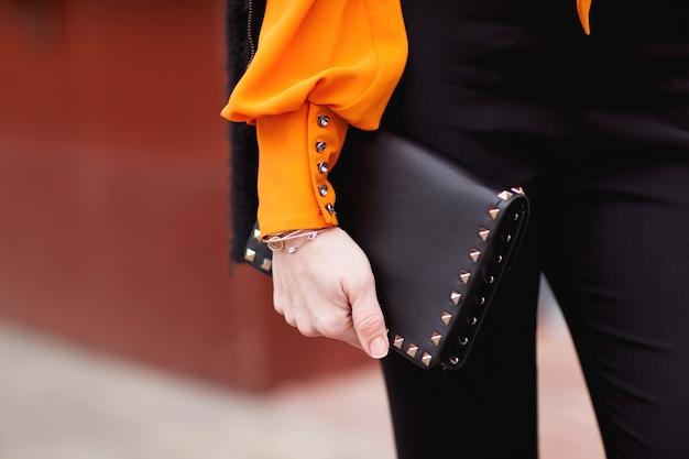 Het meisje houdt een zwarte handtas vast