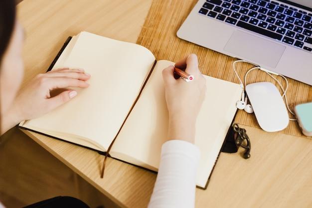 Het meisje houdt gegevens bij in haar dagboek, zaken doen en zaken doen, met behulp van een computer en een notebook