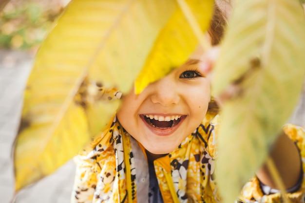 Het meisje houdt gele bladeren vast en kijkt erdoorheen