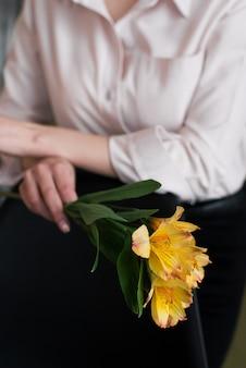 Het meisje houdt gele bloemen in de rivier. lentebloemen in de handen van het meisje.