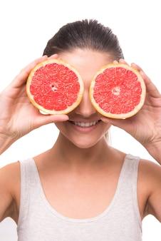 Het meisje houdt grapefruit in haar ogen en glimlacht.