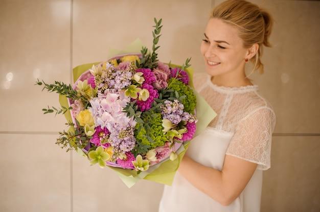 Het meisje houdt groot boeket van verschillende bloemen