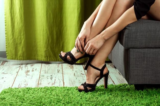 Het meisje houdt haar benen vast, de pijn in haar benen van de hielen