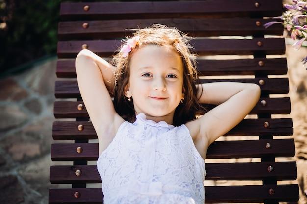 Het meisje houdt haar handen op buiten liggend op houten bank