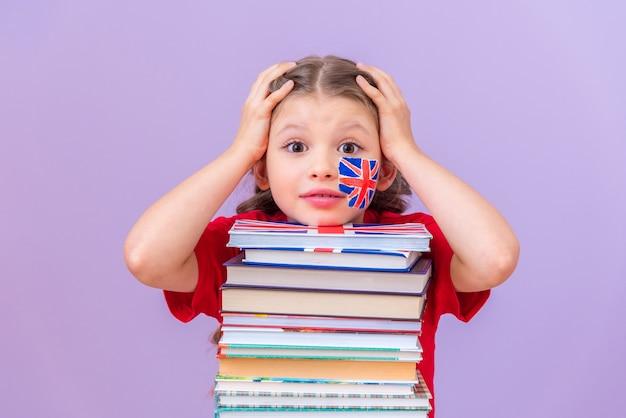 Het meisje houdt haar hoofd vast vanwege een moeilijke studie, leunend op een stapel boeken.