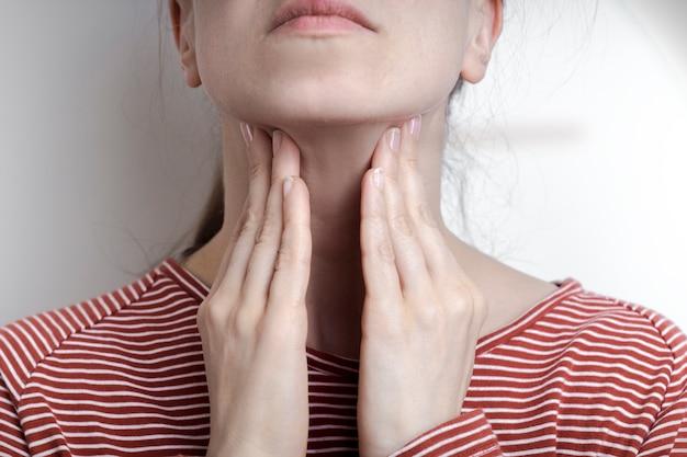 Het meisje houdt haar zere keel vast. angina.
