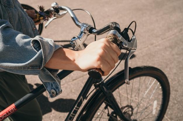 Het meisje houdt het stuur van de fiets vast. een man rolt een fiets.