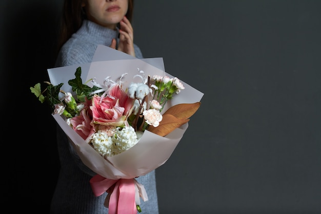 Het meisje houdt in haar handen origineel boeket in uitstekende stijl, groetachtergrond of concept