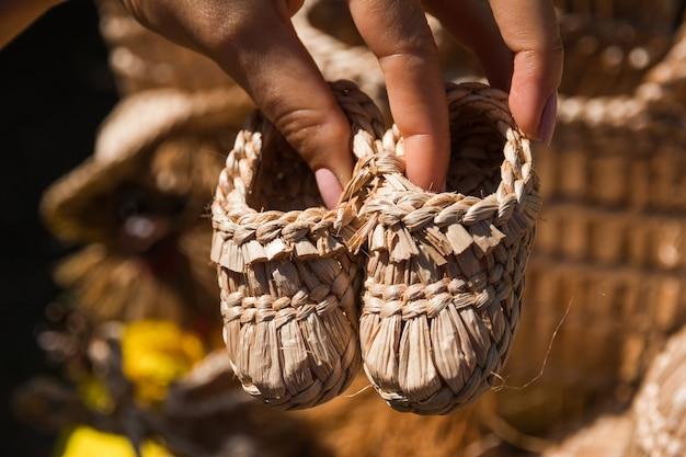 Het meisje houdt in haar handen souvenir handgemaakte kinderschoenen gemaakt van stro voor festivals van volkskunst en ambachten