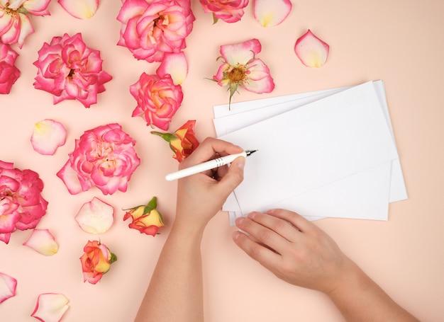 Het meisje houdt in haar linkerhand een witte pen en ondertekent enveloppen op een perzikachtergrond