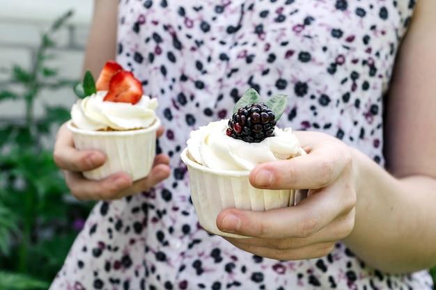 Het meisje houdt in handen cupcakes met slagroom en aardbeien en braambes.