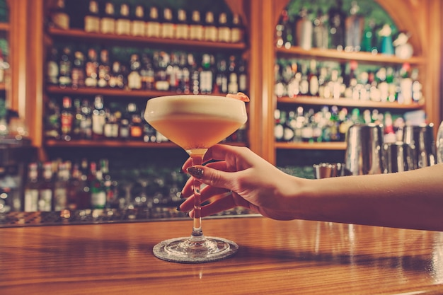 Het meisje houdt in zijn hand een glas alcoholische drank aan de bar