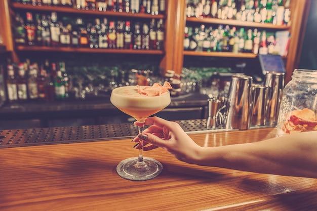 Het meisje houdt in zijn hand een glas alcoholische drank