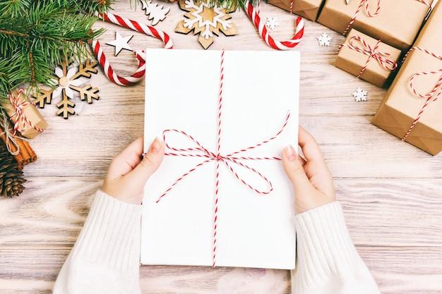 Het meisje houdt kerstbrieven voor kinderen. kerstmisbrieven met giftvakje en kerstmisdecoratie. afgezwakt