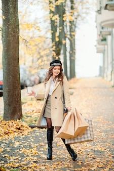 Het meisje houdt papieren ambachtelijke pakketten in de herfst
