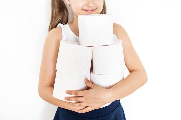 Het meisje houdt rollen wc-papier, huis, voorraden in geval van quarantaine, thuis zitten, verzorging en hygiëne, toiletartikelen, netheid, comfort, schone handen, sanitair