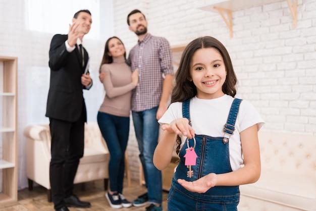 Het meisje houdt sleutels van huis terwijl makelaar in onroerend goed flats toont.