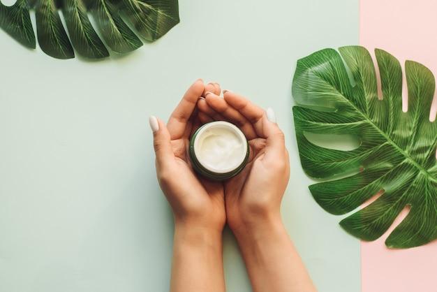 Het meisje houdt vochtinbrengende crème in haar handen op een achtergrond van verse palmbladen. het concept van natuurlijke cosmetica gemaakt van tropische ingrediënten