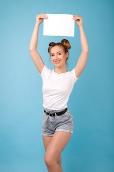 Het meisje houdt witte affiche boven haar hoofd op blauwe ruimte