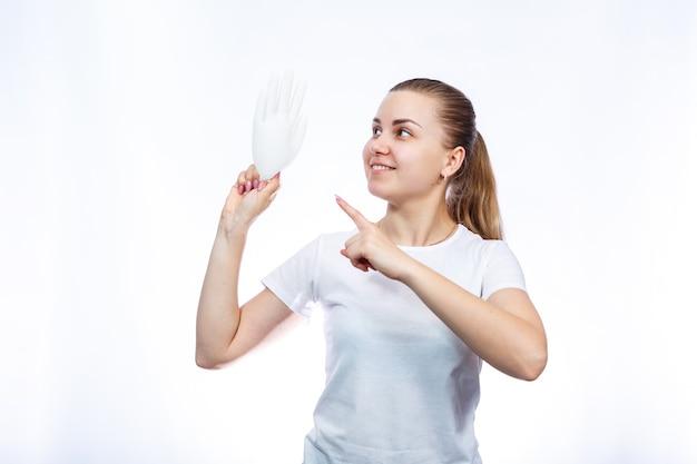 Het meisje houdt witte medische handschoenen in haar handen. bescherming tegen ziektekiemen en het virus. ze is in een wit t-shirt op een witte achtergrond.